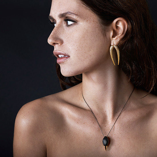 Image of model wearring Hades Necklace Gold/Black and Echoes of the Lyre Earrings gold from NIOMO´s Eurydice Collection. The pieces are made from sterling silver and plated in 18 karat yellow gold and black rhodium.